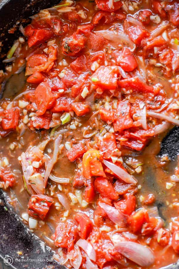 Tomato sauce with spices combined and cooking in a skillet