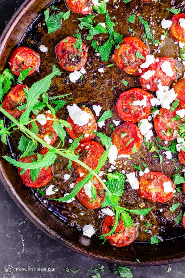 Quick Oven-Roasted Tomato with Thyme and Feta | The Mediterranean Dish. In just 20 minutes you can have the perfect side dish of tomatoes. Tossed in olive oil, lemon juice and thyme. Roasted to perfection and then garnished with feta and your choice of fresh herb. Simple never tasted better!