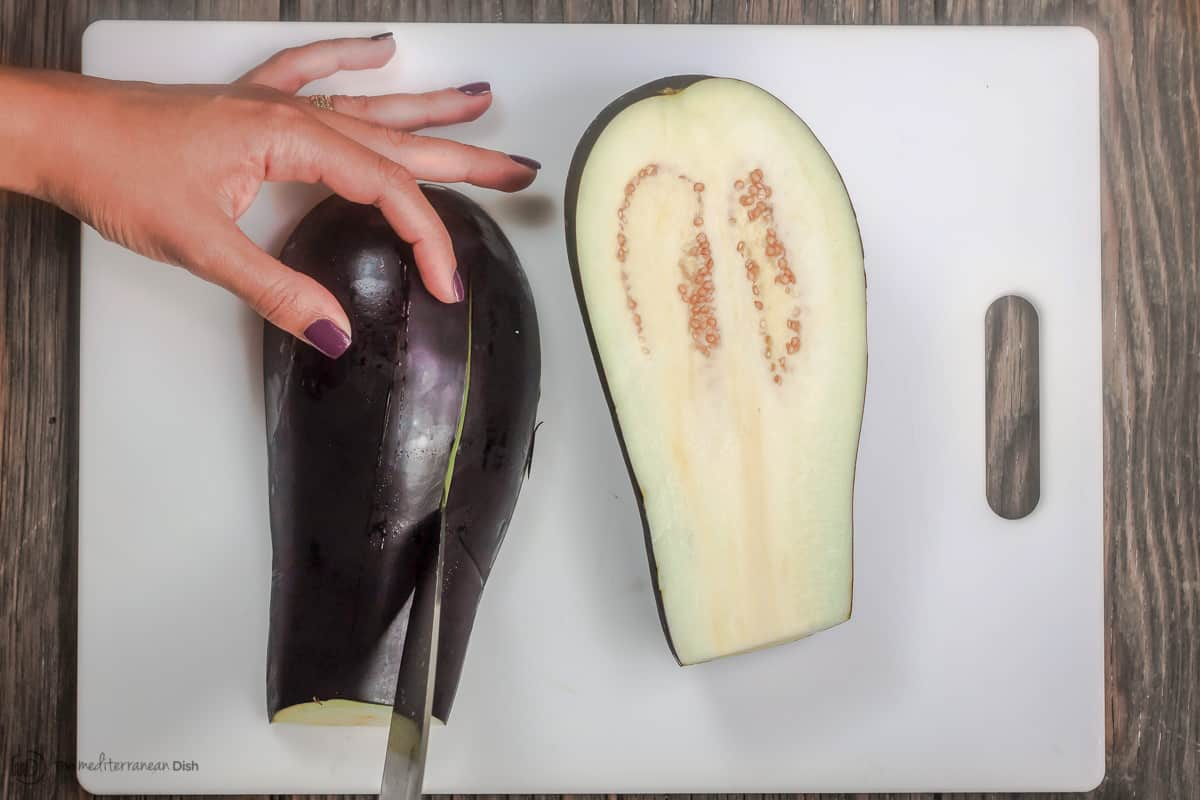 Eggplant being sliced on a cutting board.