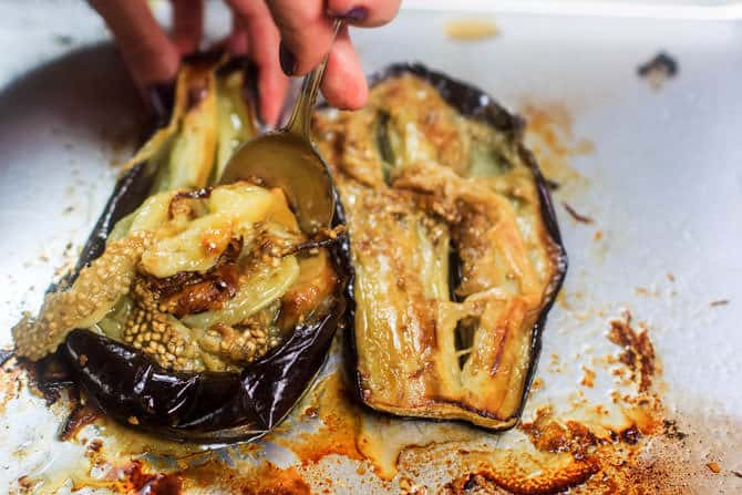 eggplant flesh being scooped up with a spoon