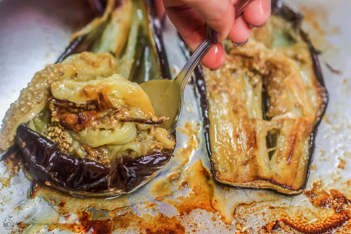 Roasted eggplant flesh being scooped up with a spoon. Skin discarded