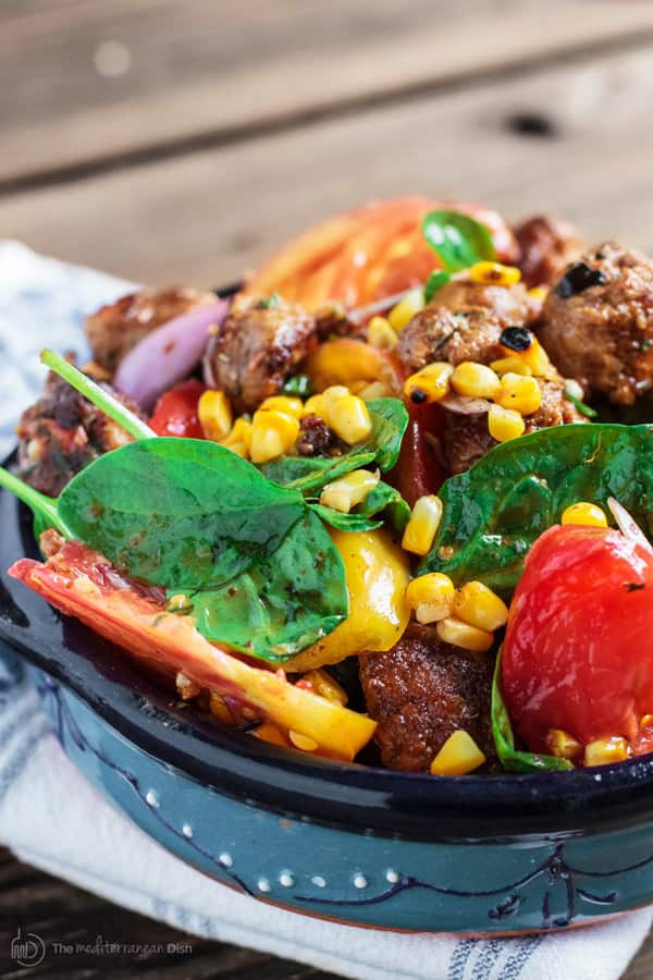 Spinach salad garnished with corn, tomatoes and chorizo