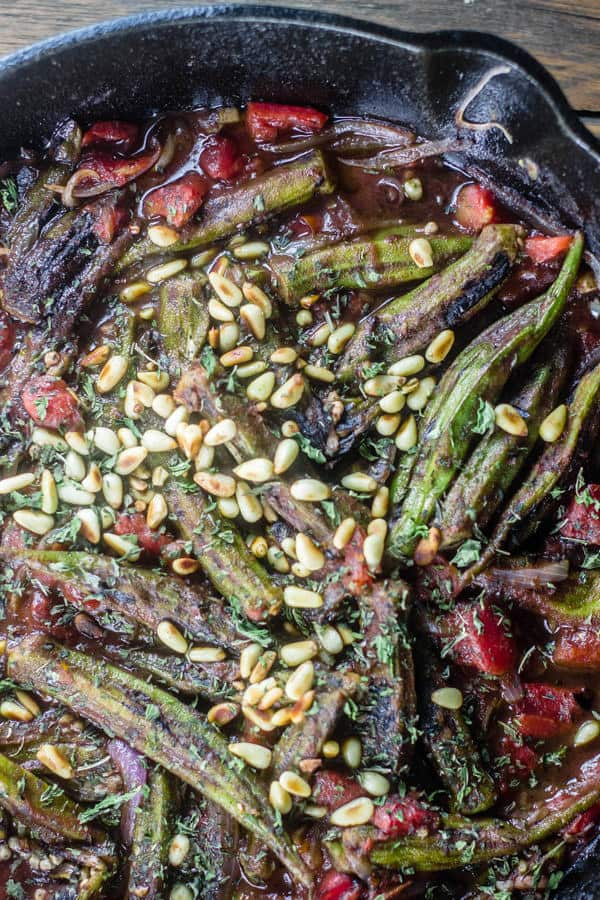 Okra, tomatoes, and pine nuts, onions and garlic cooking together in a pan