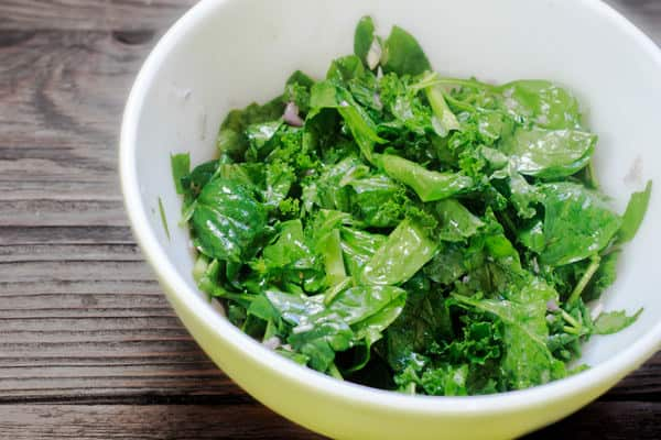 Spinach and kale in a bowl with vinaigrette