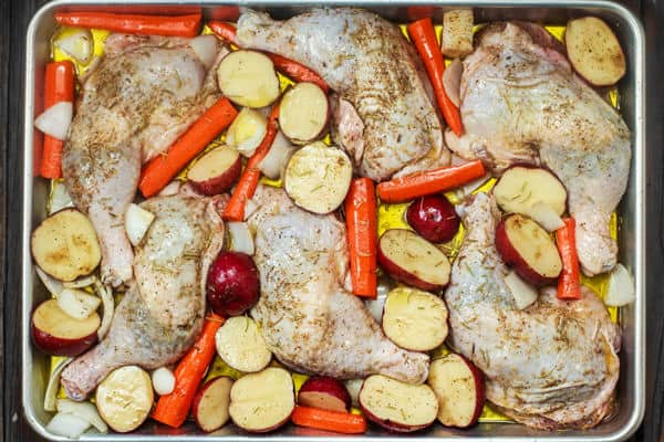 Chicken thighs and vegetables seasoned and combined in a baking pan