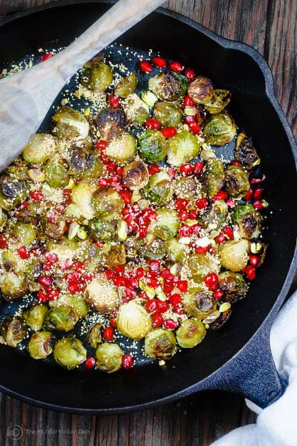 Roasted Brussels Sprouts with Bulgur and Pomegrantes | The Mediterranean Dish. This simple recipe takes brussels sprouts to a new level! Brussels sprouts carmalized to perfection, dressed in a slash of lime juice and tossed with bulgur wheat and pomegranate seeds. The perfect holiday side dish or pick-me-up salad! Try it soon!
