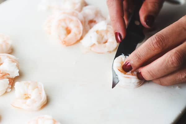 Shrimp being cut in half length-wise