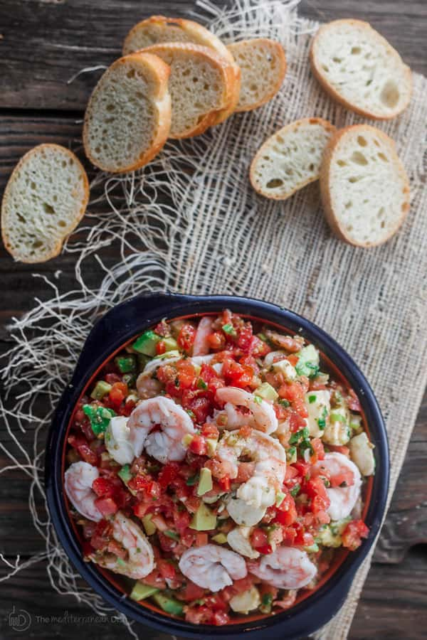 Shrimp Bruschetta Recipe | The Mediterranean Dish. Not your average bruschetta. Fresh tomatoes tossed with shrimp, avocado, green onions, garlic and a good quality basil pesto! A festive and more satisfying appetizer in minutes.
