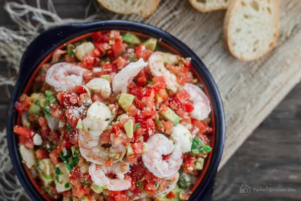 Bowl of combined ingredients for Shrimp Bruschetta with bread on the side