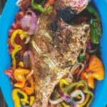 Roasted whole red snapper placed on a bed of vegetables in a dish