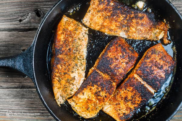 Salmon fillets being cooked in a pan