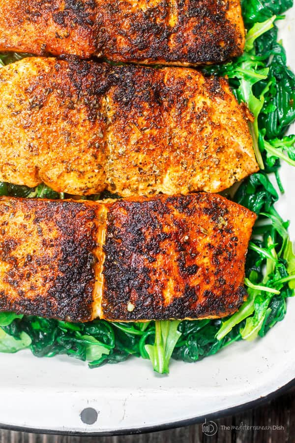 Close-up of Pan Seared Salmon fillets over a bed of greens
