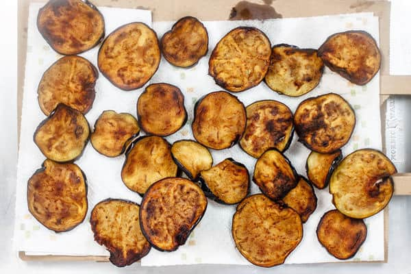 Fried eggplant slices placed on paper towels to drain excess oil