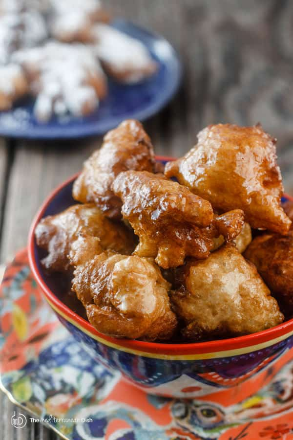 Two servings of donuts, one covered in cinnamon syrup and other in powdered sugar