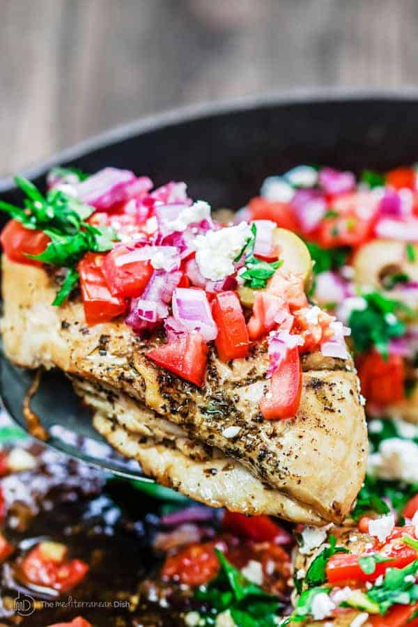 One-Skillet Mediterranean Chicken Recipe | The Mediterranean Dish. This Greek-inspired chicken dinner comes together in 15 minutes! Four chicken breasts and a few flavor-packed ingredients is all you need!