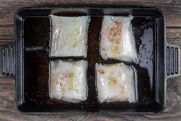 Pieces of cod on baking sheet ready to be baked