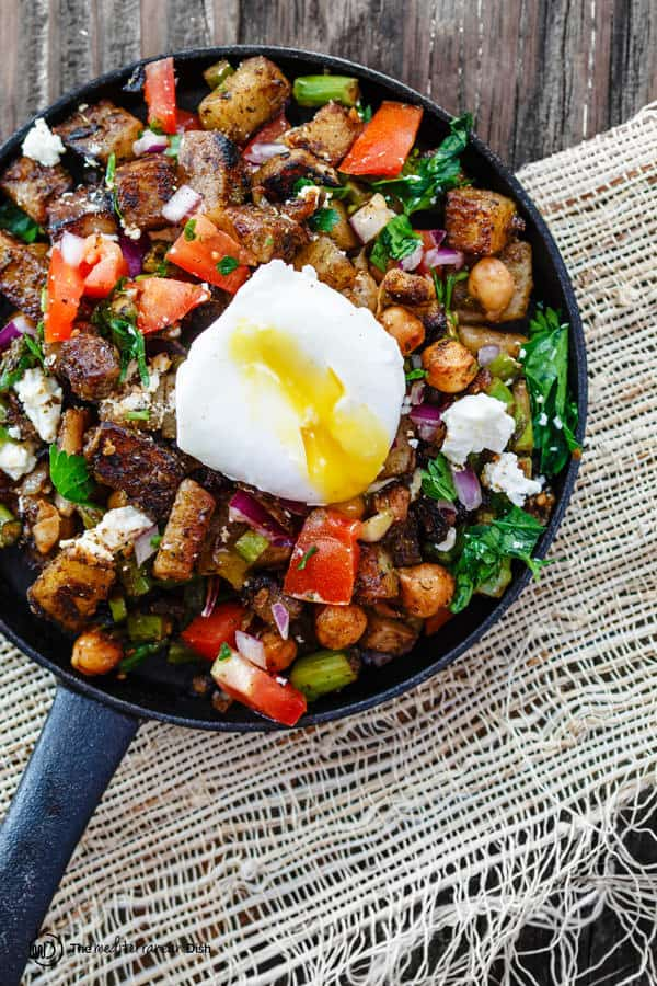 Mediterranean Potato Hash in skillet with toppings and broken poached egg
