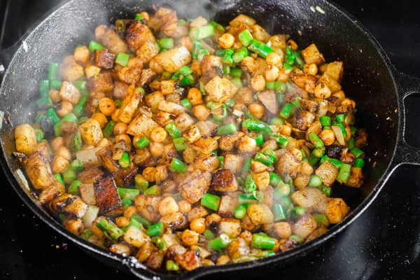 Ingredients of potato hash cooking in skillet