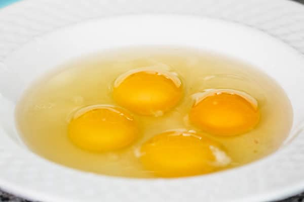 Four raw eggs with egg whites in bowl