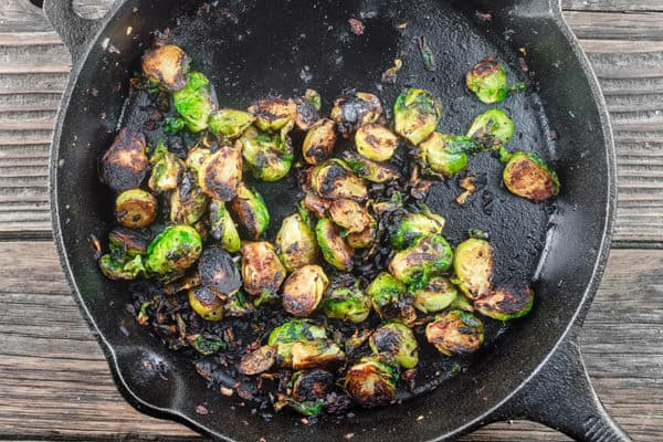 Fried Brussels Sprouts Recipe with Onions and Quick Polenta | The Mediterranean Dish. Crispy brussel sprouts fried in olive oil; served with Parmesan polenta and topped with toasted pine nuts. A 20-minute delicious side dish!