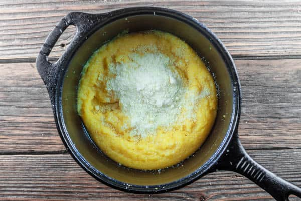 Parmesan cheese added to the pot of cooked polenta