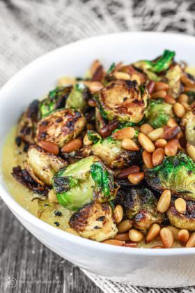 Fried Brussels Sprouts Recipe with Onions and Quick Polenta   The Mediterranean Dish. Crispy brussel sprouts fried in olive oil; served with Parmesan polenta and topped with toasted pine nuts. A 20-minute delicious side dish!