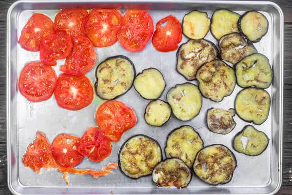 Slices of eggplant and tomatoes lined on a baking sheet