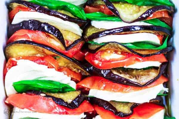 Roasted Eggplant Caprese Salad Recipe | The Mediterranean Dish. A satisfying appetizer or even side dish! Roasted eggplants, tomatoes, and melted mozzeralla cheese with basil nestled in between. Dressed in a simple basil viniagrette! See the step-by-step tutorial on The Mediterranean Dish