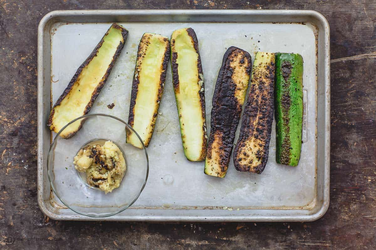 Grilled zucchini halves. Some zucchini flesh scooped out on the side to make zucchini boats