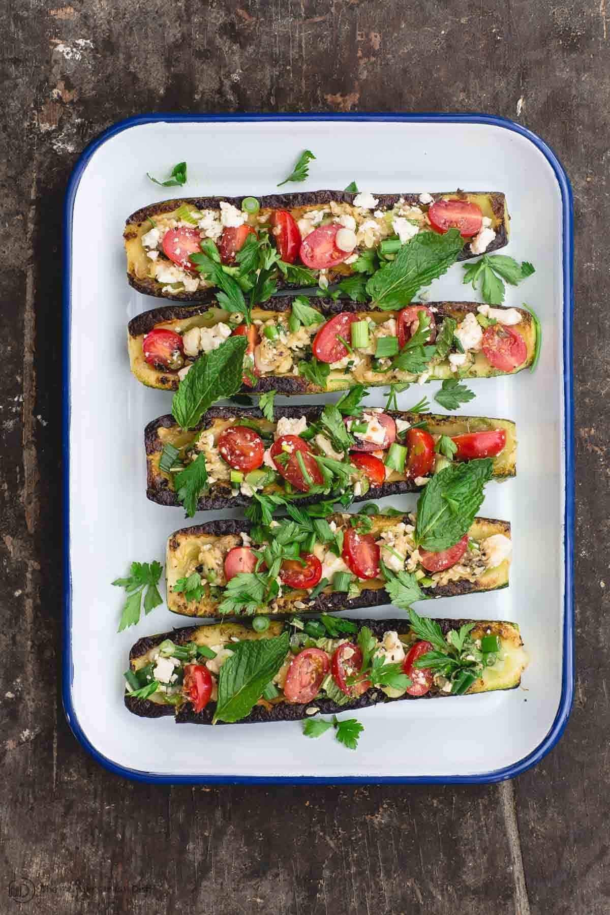 Grilled zucchini boats filled with tomato, feta, and fresh herb mixture