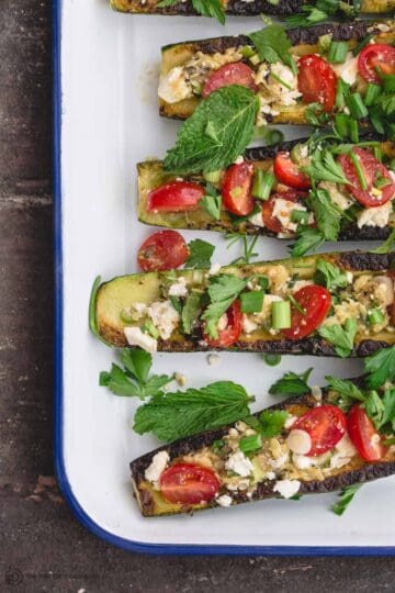 Grilled zucchini boats filled with a Mediterranean-style mixture of cherry tomatoes, feta, and fresh herbs