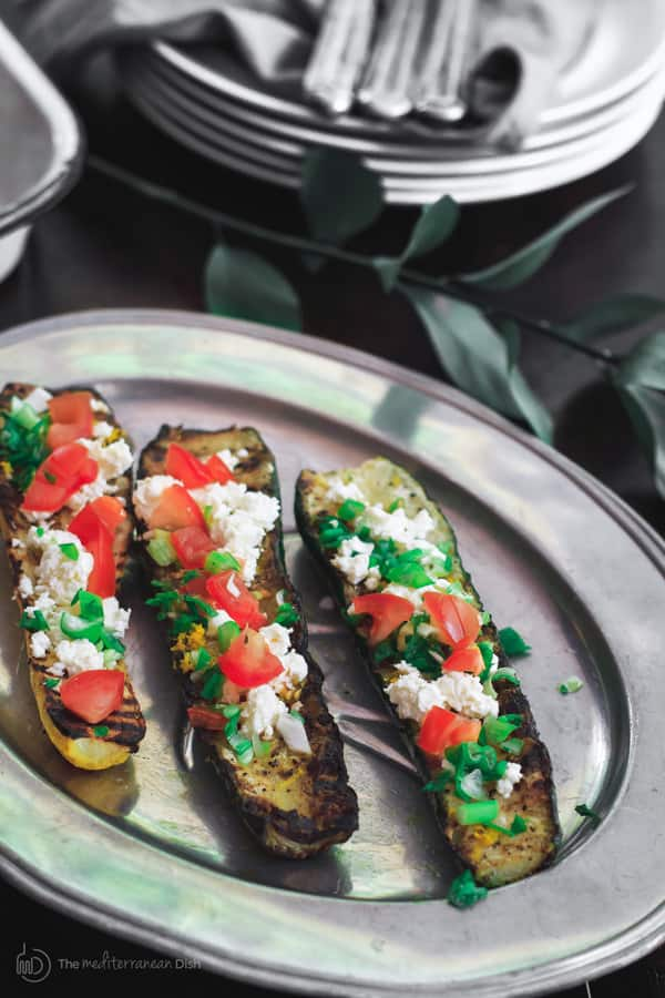 Mediterranean Grilled Zucchini Recipe | The Mediterranean Dish. Quick olive oil grilled zucchini topped with tomato, feta and green onions. Comes together in less than 15 minutes! The perfect appetizer or side dish. See it on TheMediterraneanDish.com