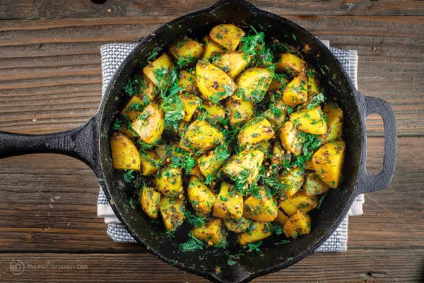 Batata Harra served in skillet with more fresh herbs on top