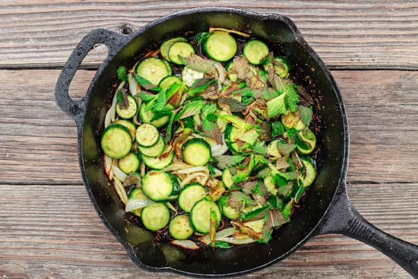 Zucchini, onions and mint added to a skillet