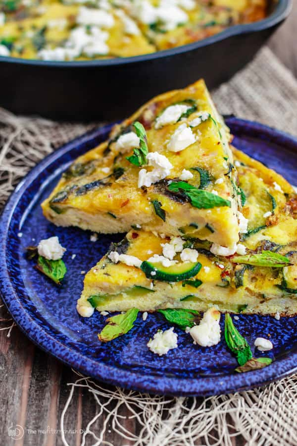 Slice of Middle Eastern Zucchini Baked Omelet garnished with basil leaves and feta cheese
