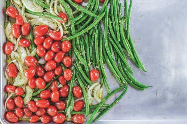 Green beans, cherry tomatoes, and onions added to sheet pan