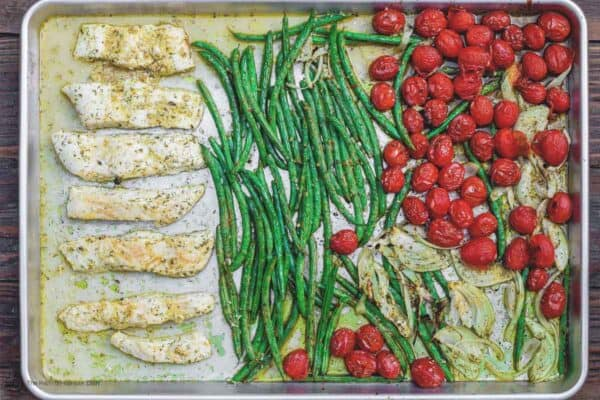 halibut and vegetables spread on sheet pan