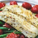 Baked halibut served in a plate with tomatoes and green beans