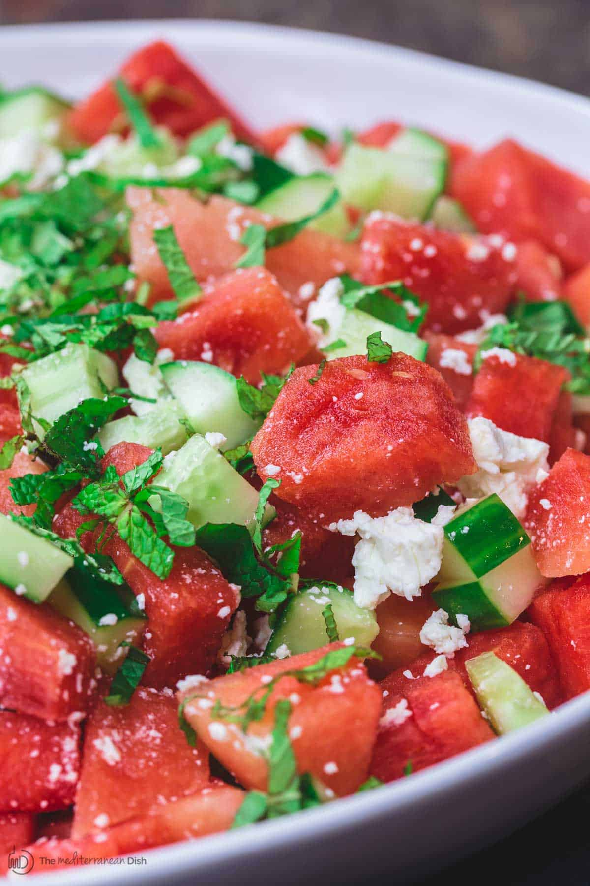 Mediterranean Watermelon Salad Recipe | The Mediterranean Dish. A light and fresh watermelon salad with cucumbers, feta cheese and fresh herbs. All dressed in a honey vinaigrette.