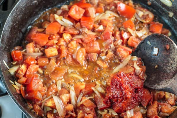 Harissa paste is added to the pan and cooked in with the onions