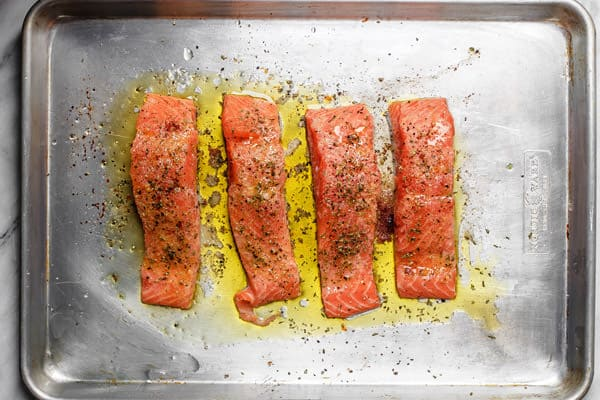 Salmon fillets placed on a baking sheet and drizzled with olive oil