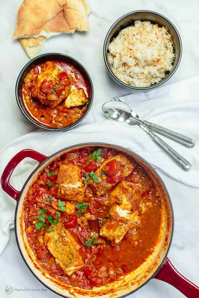 Cod fish fillet cooked with tomato sauce in braiser, served next to a bowl or rice
