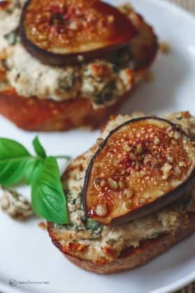 Fig Pistachio Goat Cheese Crostini | The Mediterranean Dish. A Mediterranean style goat cheese corstini recipe with pistachios, walnut, basil, figs and a touch of molasses. An easy and impressive appetizer! See it on TheMediterraneanDish.com
