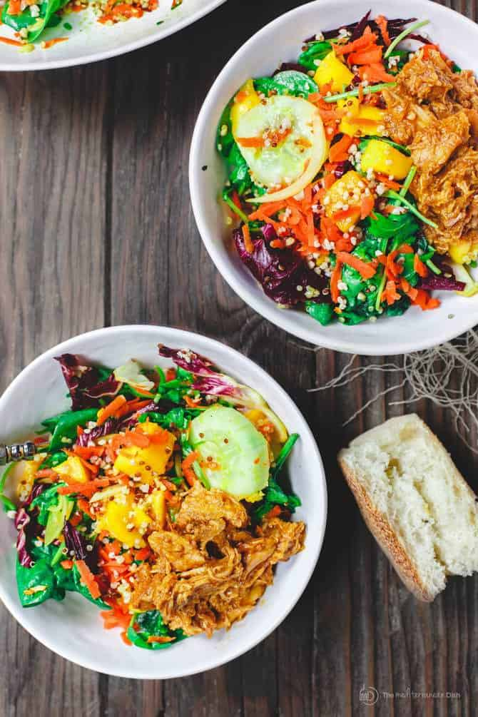 Two servings of Spinach Quinoa Mango Salad served with bread