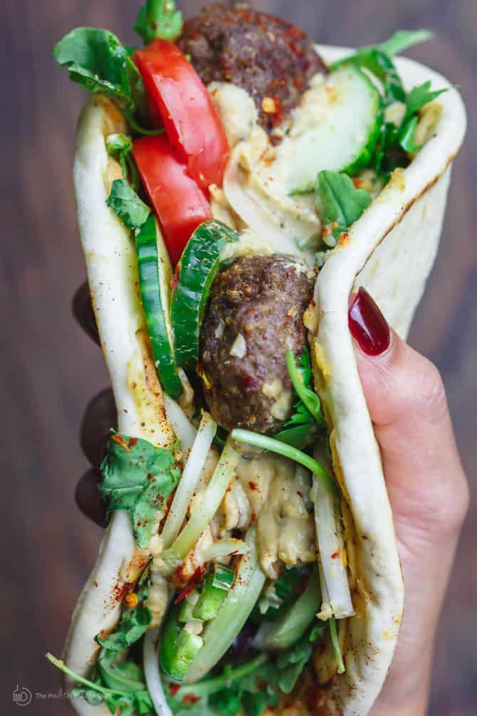 Baked Kofta Pita Sandwich | The Mediterranean Dish. Baked ground lamb kofta patties, flavored with warm Mediterranean spices, served on Greek pita with fresh veggies and hummus spread. Make it for an easy dinner, or setup a make-your-own-sandwich bar for your next party! See it step-by-step on TheMediterraneanDish.com