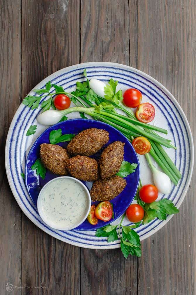 5 pieces of Kibbeh served on a plate with dip and vegetables