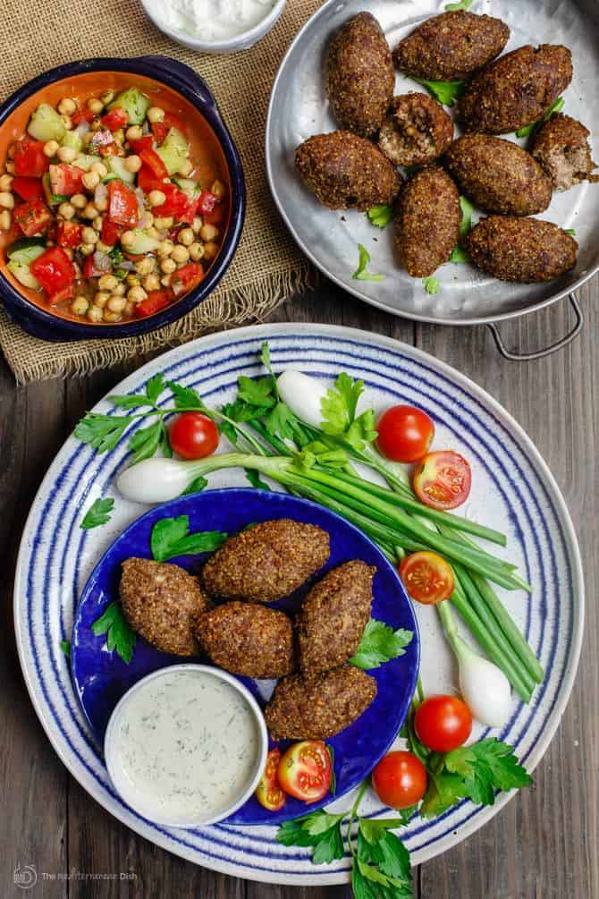 Kibbeh served with a side of mixed vegetables and Greek dip