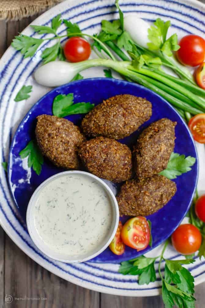 Kibbeh on a plate served with Greek dip
