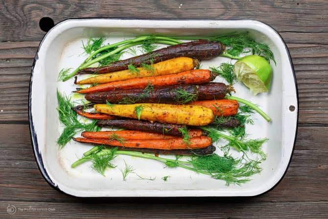Carrots in a baking dish garnished with dill and parsley