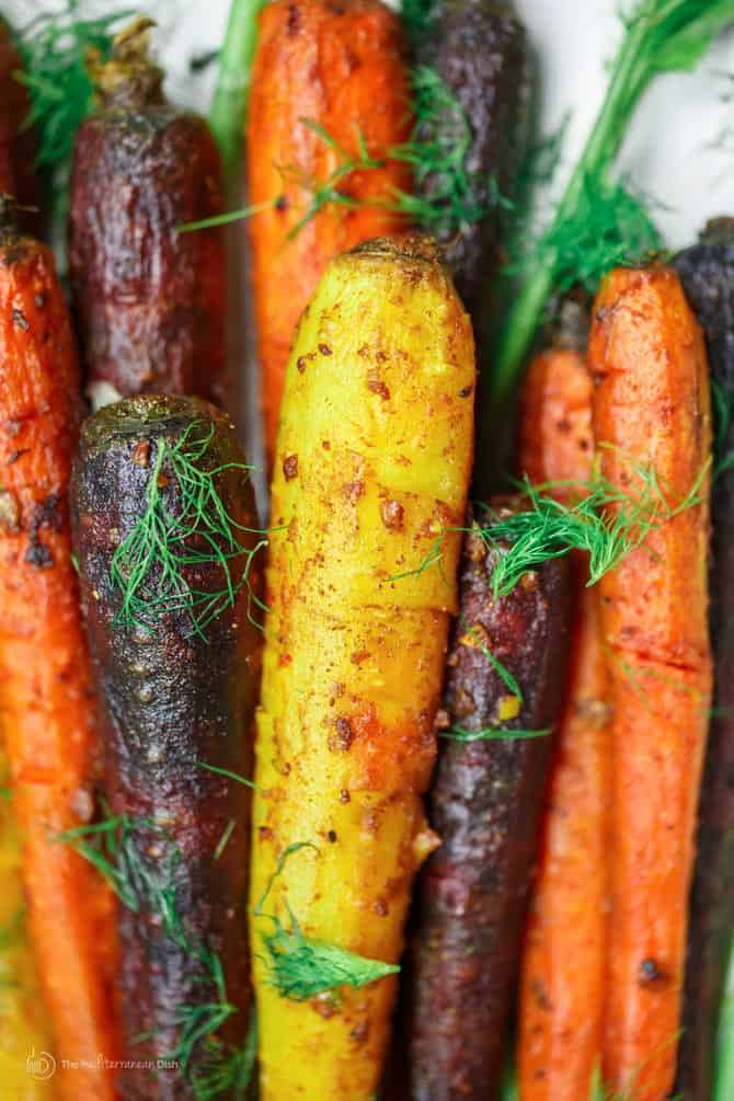 Turmeric Roasted Carrots Recipe | The Mediterranean Dish. A simple side dish of whole roasted carrots prepared the Mediterranean way w/ olive oil, lime juice, garlic and spices like turmeric and cinnamon. A healthy and easy side dish that wins every time! See it on TheMediterraneanDish.com